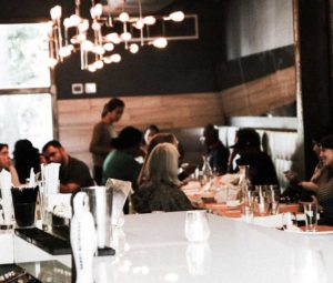Interior dining area with customers and attentive server