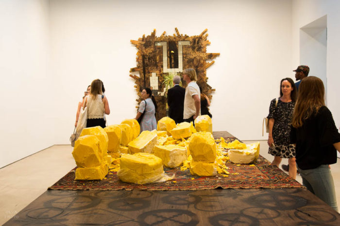 Untitled (Shea Butter-table) with falling man series at the back by Rashid Johnson