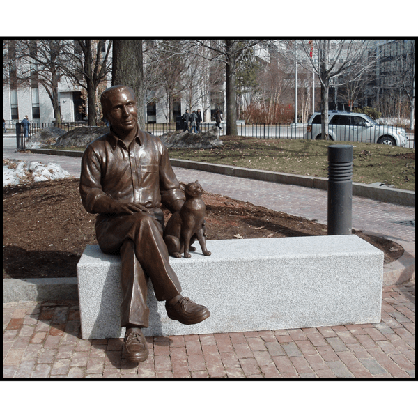 photo of bronze-colored sculpture of seated man crossing his legs petting the cat beside him
