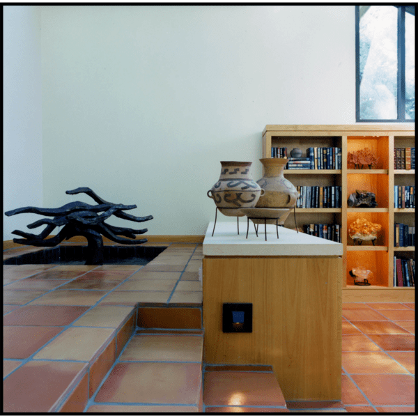 photo of bronze-colored small indoor fountain with flowing shapes, in white-walled room with tiled floor, tiled steps, and wooden shelves and bookcases