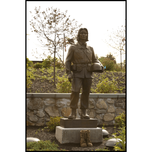 photo of bronze-colored sculpture of soldier in garden setting with rock wall behind