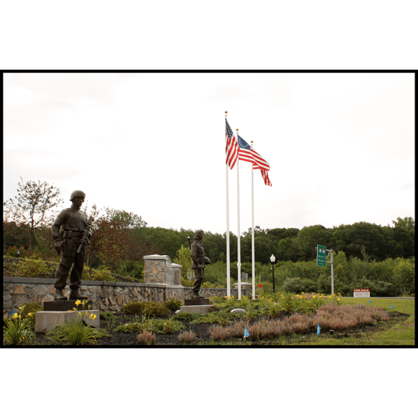 photo of garden setting and rock wall, flags, and trees behind with two bronze-colored sculptures of soldiers