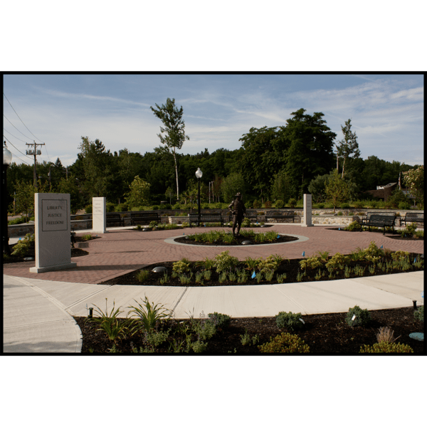 photo of park with hardscaping and landscaping with bronze-colored sculpture of soldier in the center