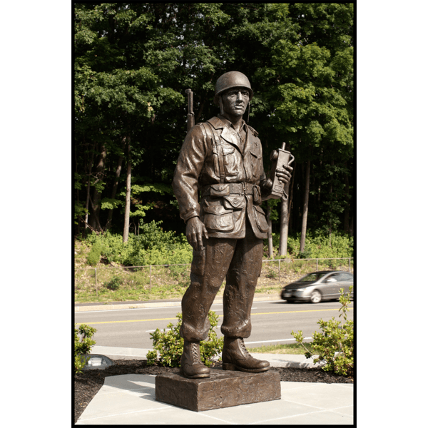 photo of bronze-colored sculpture of soldier in park setting