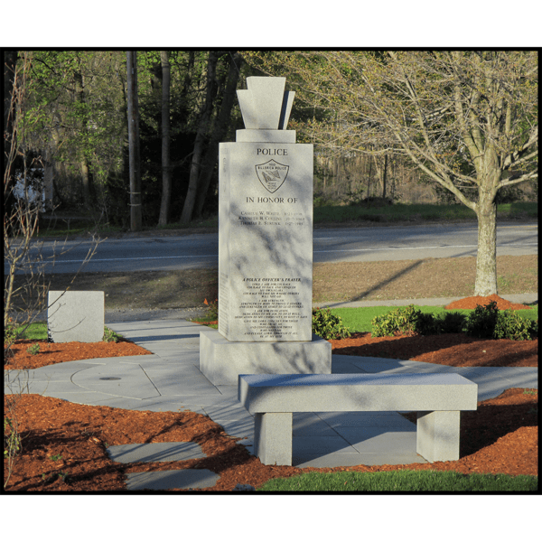 photo of granite memorial surrounded by hardscaping, landscaping, and granite benches