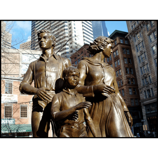 closeup photo of bronze-colored sculpture of male, female, and child in movement on round stone base in hardscaped plaza with buildings and streets surrounding it