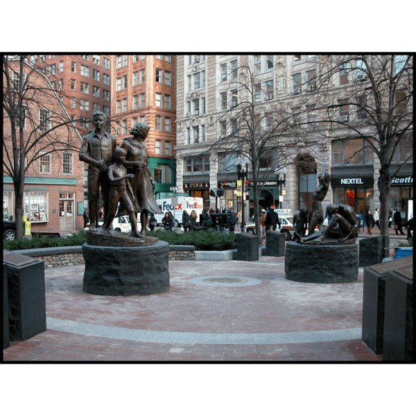 photo of two bronze-colored sculptures of a male, female, and child in movement on round stone bases in hardscaped plaza with buildings and streets surrounding it