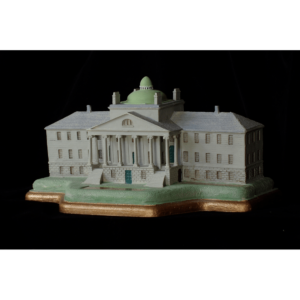 photo of sculpture of a white building with pediment, columns, and dome atop green land on a bronze-colored base