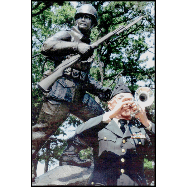 photo of bronze-colored sculpture of soldier holding rifle in action on incline with trees behind and veteran in dress uniform in front playing trumpet