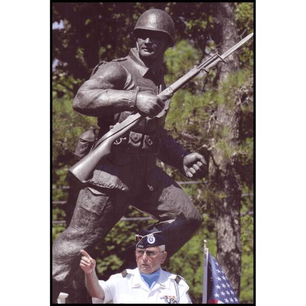 photo of bronze-colored sculpture of soldier holding rifle in action on incline with trees behind and veteran in dress uniform in front
