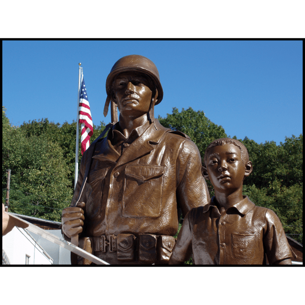 photo of bronze-colored sculpture of American male soldier and Korean boy with flag and trees behind