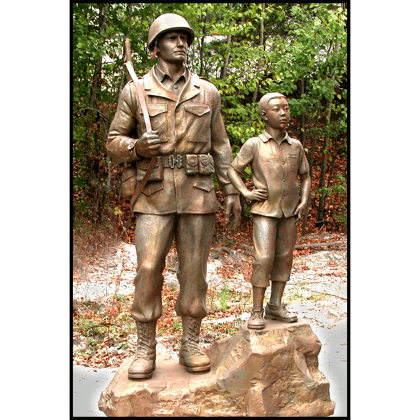 photo of bronze-colored sculpture of American male soldier and Korean boy posed on natural-looking rock with trees behind