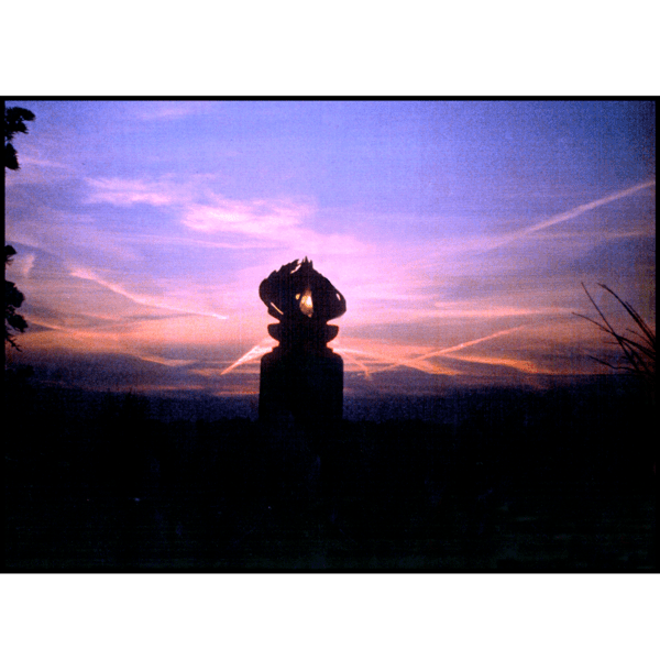 photo of purple and pink sunset and silhouette of bronze sculpture of flame on black granite base with surrounding trees