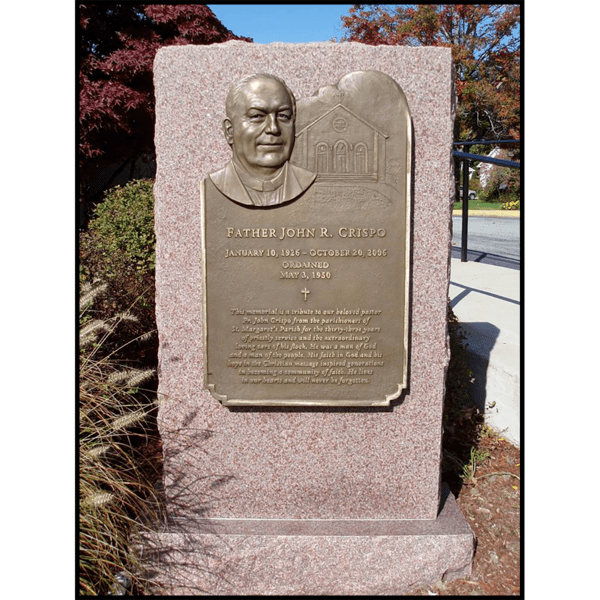 photo of bronze-colored plaque with portrait of John Crispo mounted on granite in landscaped area with walkway with railing and trees behind