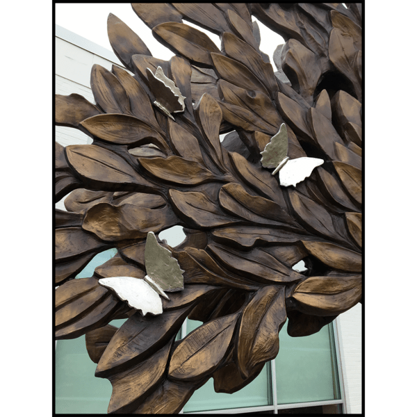 closeup photo of bronze-colored tree sculpture with silver-colored sculpted butterflies and building in background