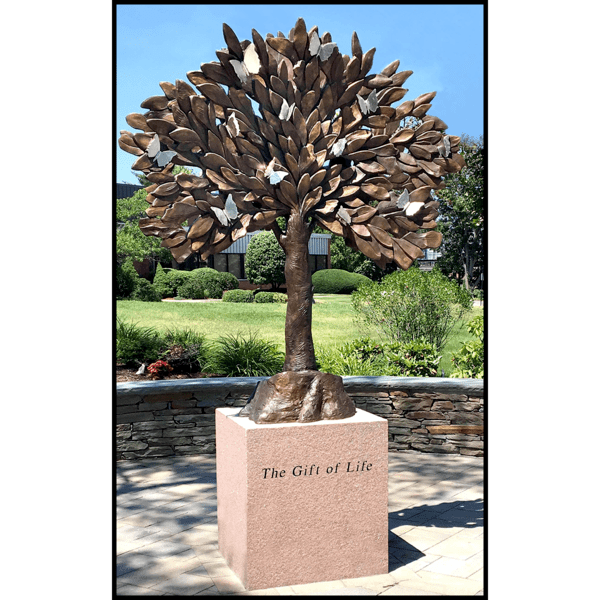 photo of bronze-colored tree sculpture on granite base in hardscaped plaza surrounded by landscaping with building in background