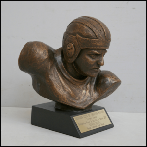photo of bronze-colored sculpture of bust of a football player with helmet atop a black base with plaque