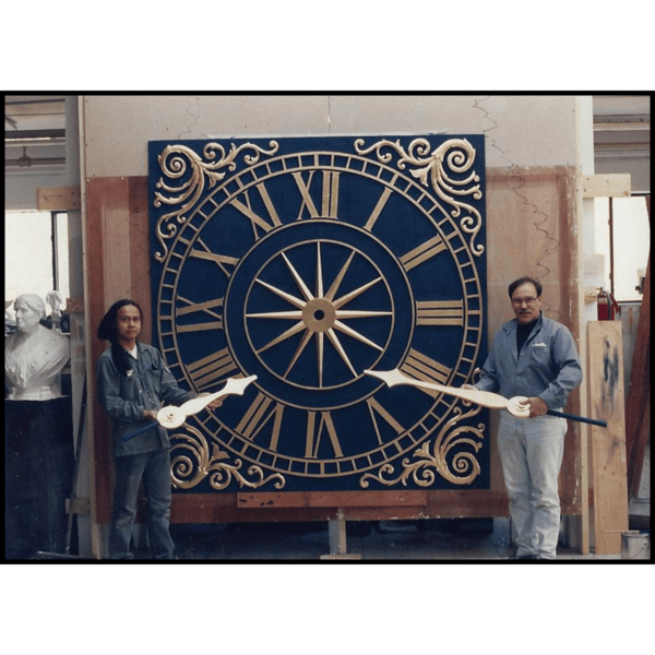photo of blue and gold clock in studio with sculptor Robert Shure and assistant standing beside it holding the gold clock hands