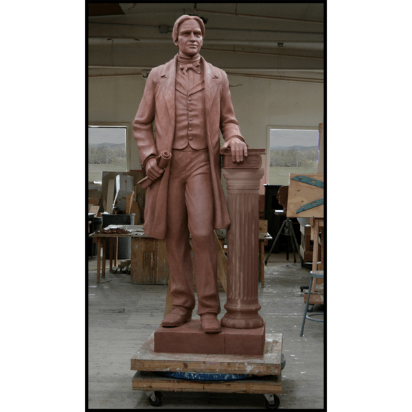 photo of clay model of statue of Horace Mann holding scroll and standing beside column with books in sculpture studio