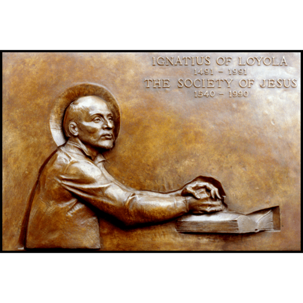 photo of bronze-colored plaque with relief of Ignatius of Loyola with hands folded on a book