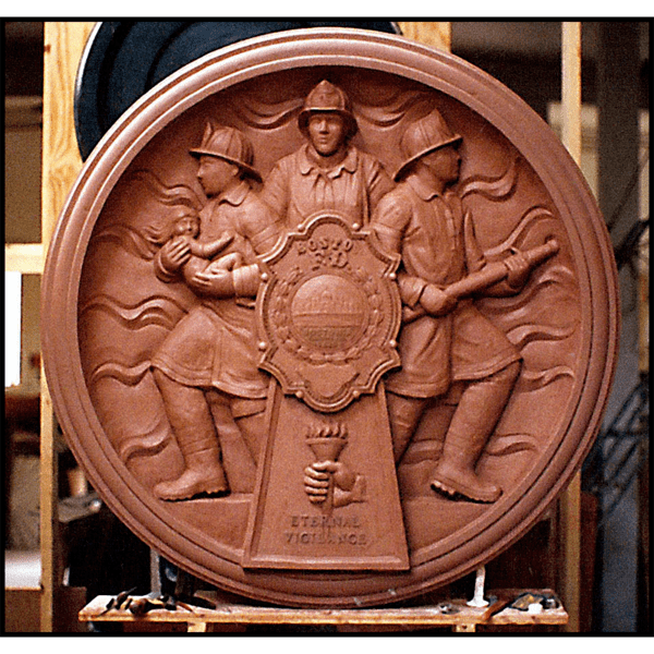 photo of clay model of relief sculpture plaque honoring Boston Firefighters with three firefighters and large fire department badge at sculptor's studio