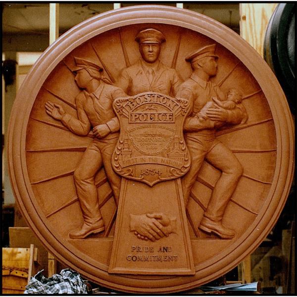 photo of clay model of relief sculpture plaque honoring Boston Police with three officers and large police badge at sculptor's studio