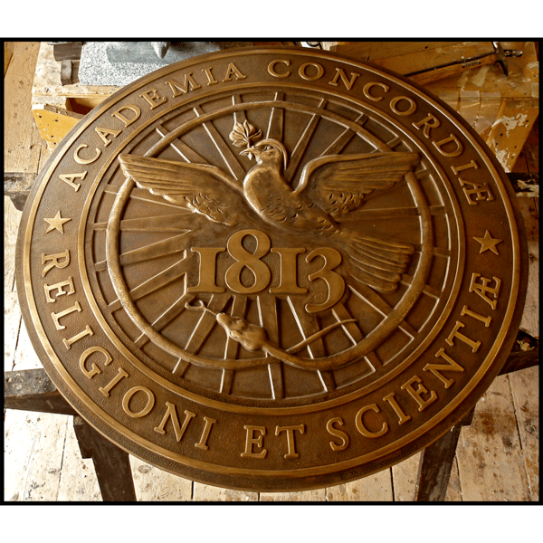 photo of bronze-colored sculpted relief of Kimball Union Academy seal featuring bird, snake, and Latin text in sculptor's studio
