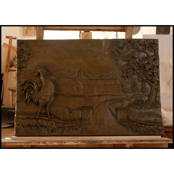 photo of bronze-colored relief plaque of farmhouse with rooster and tree in foreground in sculptor's studio