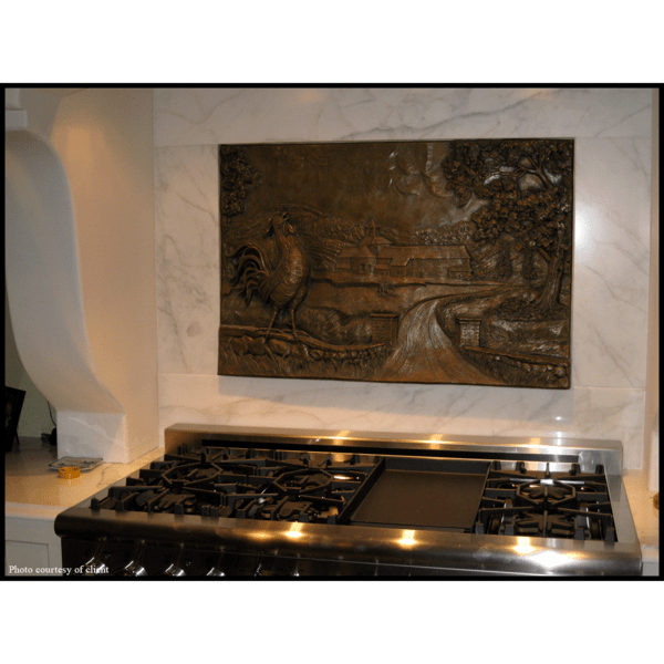 photo of bronze-colored relief plaque of farmhouse with rooster and tree in foreground mounted on tiled wall above kitchen stove