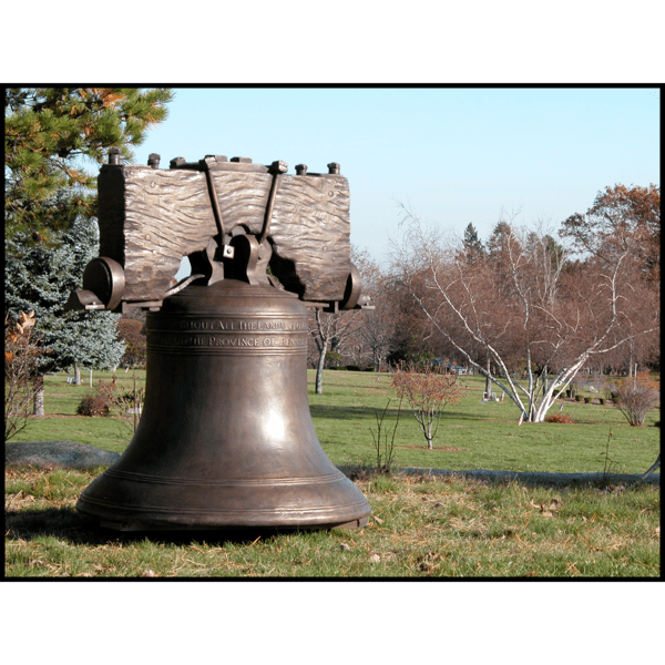photo of bronze-colored Liberty Bell with yoke in field with trees in background