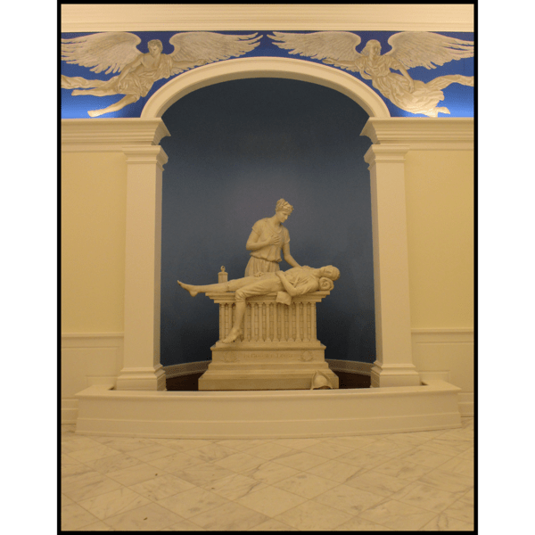 photo of white-colored sculpture of Minuteman on bier with female representing Liberty beside him in a niche with blue wall