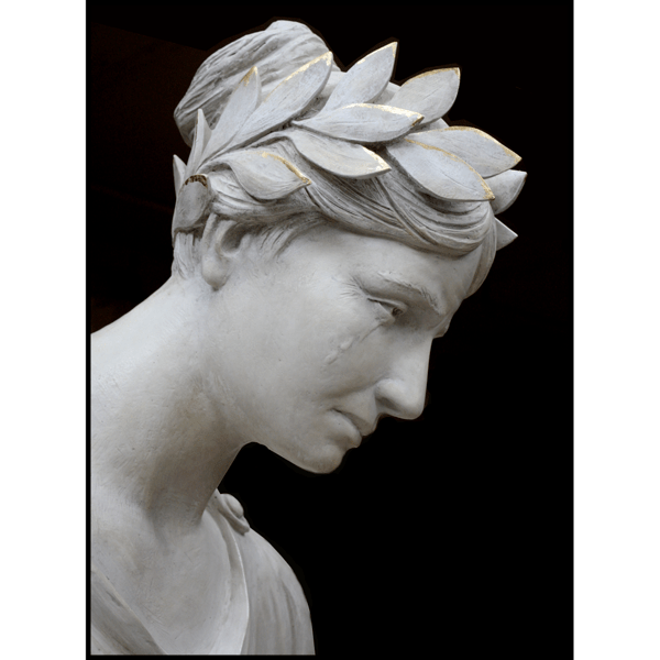 closeup photo of white-colored sculpture of female representing Liberty with crown of leaves