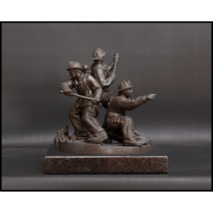 photo of bronze-colored sculpture of three firefighters in action stances on a stone base