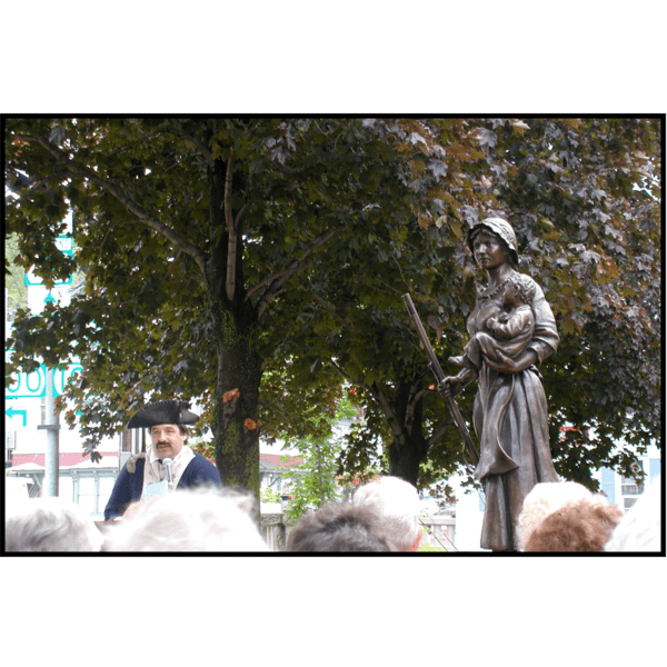 photo of person in costume and a crowd in front of bronze statue of Molly Stark holding child and musket during dedication ceremony with surrounding trees
