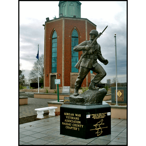 photo of bronze-colored sculpture of soldier holding rifle in action on incline on stone base in plaza and building behind