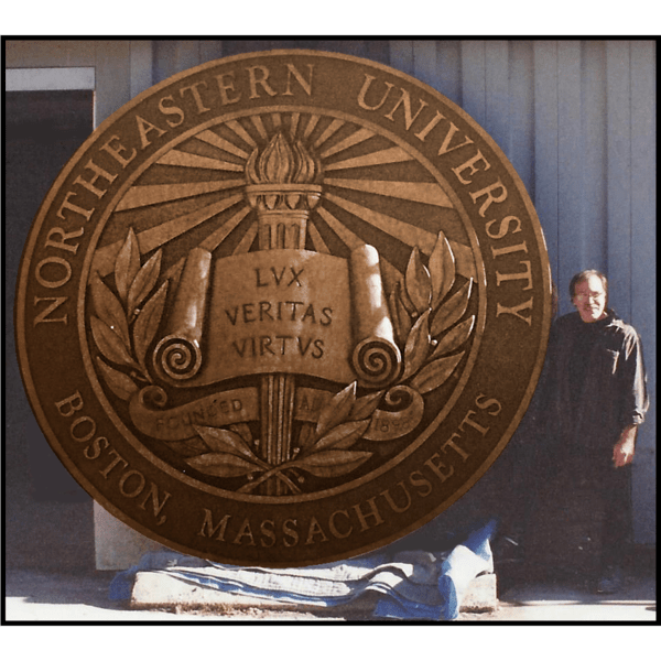 photo of bronze relief sculpture of Northeastern University's seal leaning up against wall with artist Robert Shure beside it
