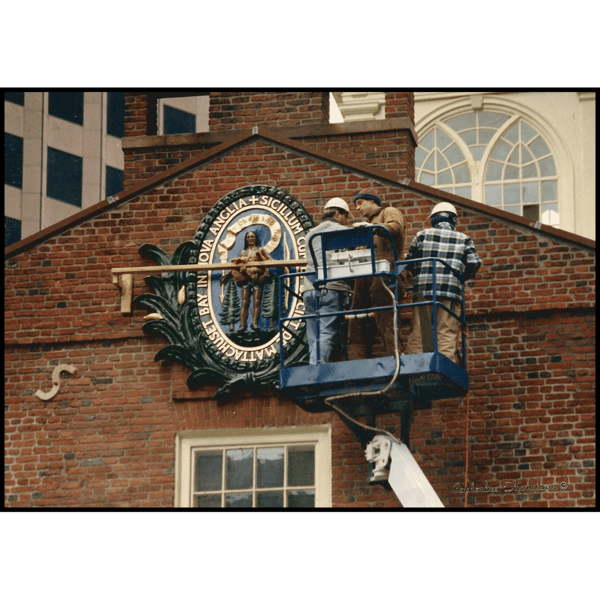 closeup of Massachusetts state seal on Boston Old State House, a brick building with off-white tower, with people on scaffolding installing it