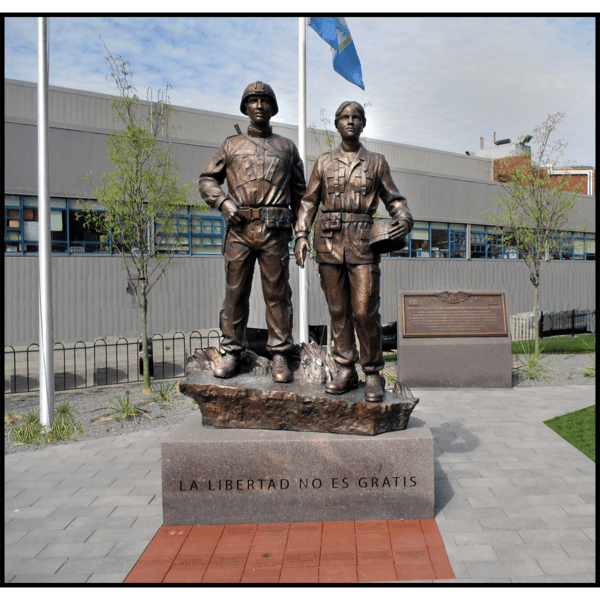 photo of bronze sculpture of two soldiers standing next to one another on low base with paving around them and building in background