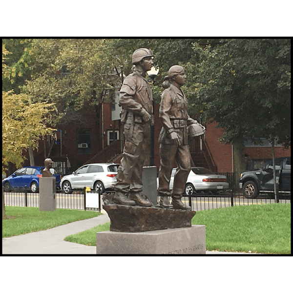 photo of bronze sculpture of two soldiers standing next to one another on low base with paving and lawn around them