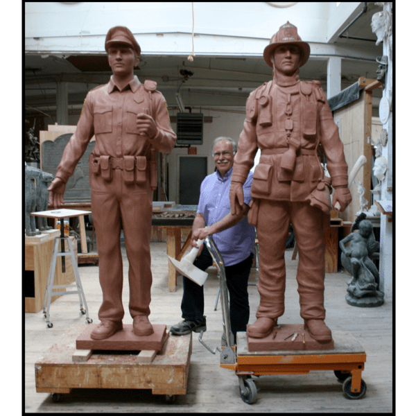photo of clay models of sculptures of a police officer and a firefighter in studio with sculptor Robert Shure in between