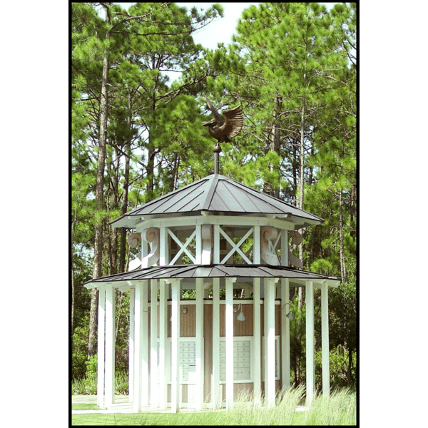 photo of gazebo-like mail kiosk with brown roofs and white supports topped with a bronze sculpture of a pelican with letter in beak and surrounded by trees and grass