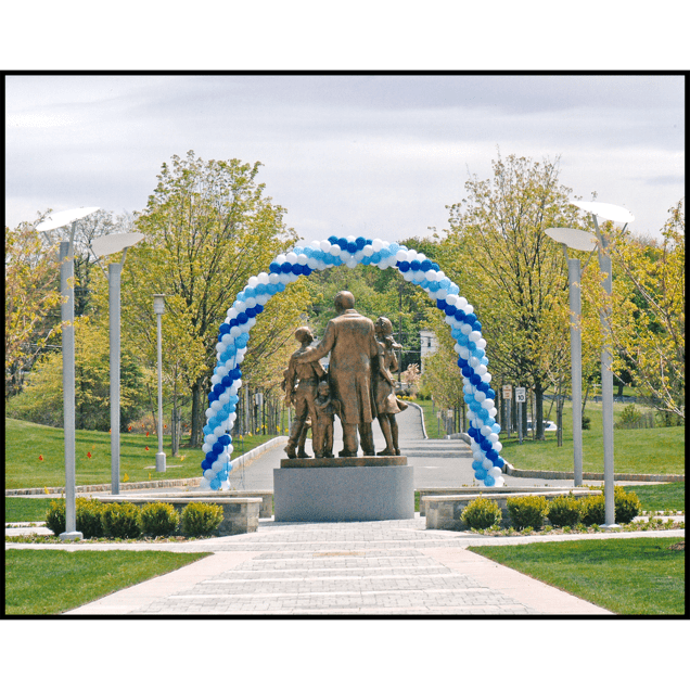 exterior photo of back of bronze sculpture figural group with blue balloon arch