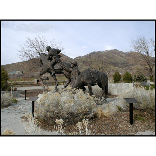 photo of bronze sculpture of galloping horse with rider and a man and another horse drinking water in a plaza with a mountain range behind