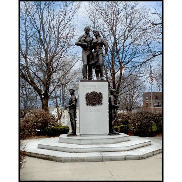 photo of monument with bronze figures of two adults and a child at the top of a tall granite pedestal and three figures around the base