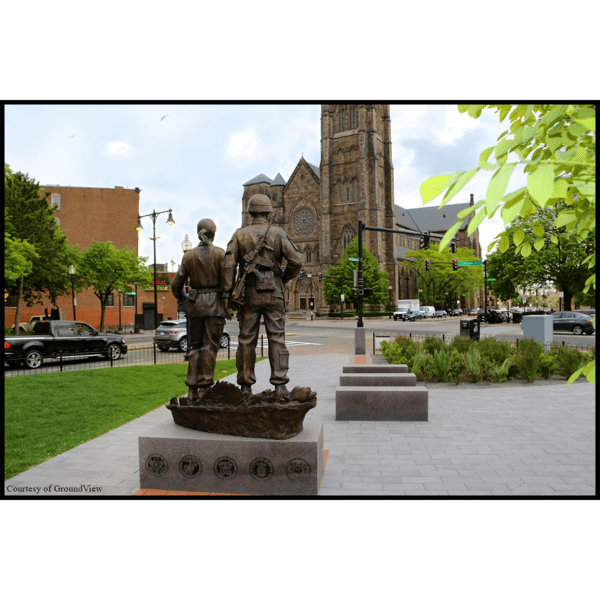 photo from the back of bronze sculpture of two soldiers standing next to one another on low base with benches in middle ground and church in background