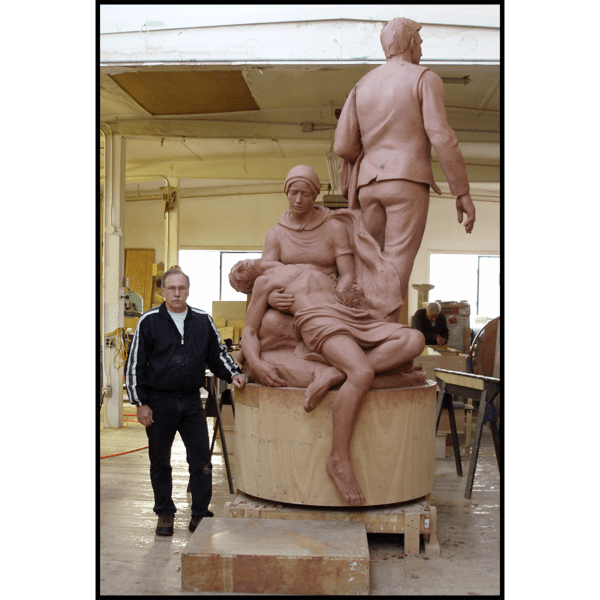 photo of clay model of figural group sculpture on round base with artist Robert Shure