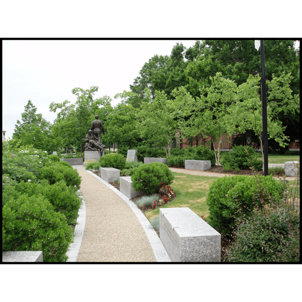 photo of bronze figural group sculpture on round stone base surrounded by pathway, shrubs, and trees