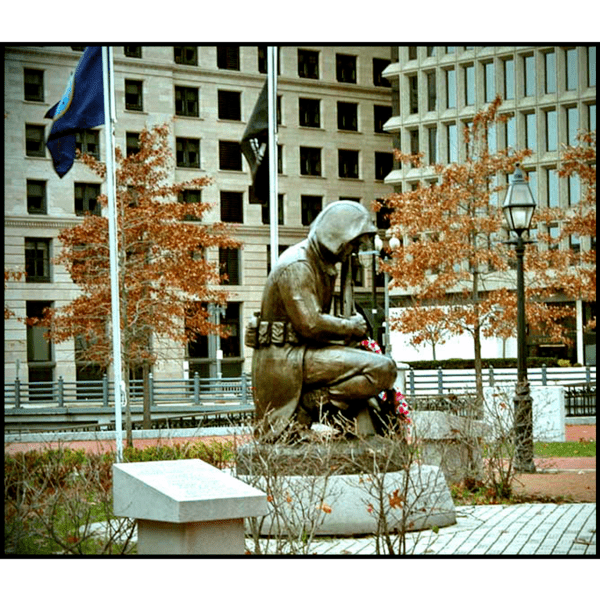 photo of bronze sculpture of kneeling Korean War soldier in coat and with gear and rifle set on a stone base in a paved area with flags and a lantern, and trees and buildings in background