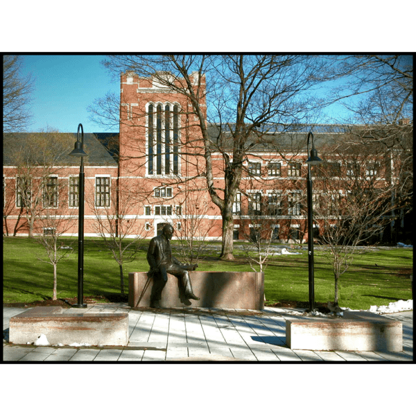 photo of bronze sculpture of Sigmund Freud sitting on a stone bench in a plaza with trees, grass, and brick building behind