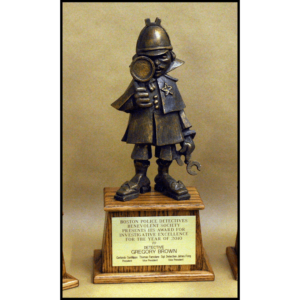 photo of bronze-colored sculpture of cartoon-like police detective atop a wood base with a plaque